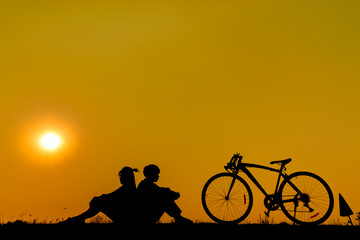 Silhouette couple sitting on grass with a bicycle on yellow sunset.
