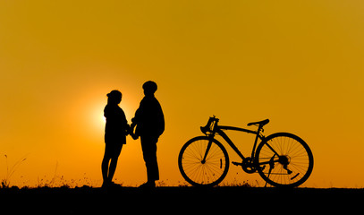 Silhouette of a couple standing and hold hand on grass with a bicycle on yellow sunset.