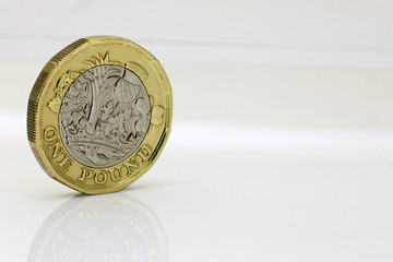 Pound coin on a reflective white surface