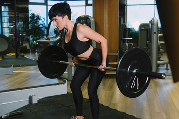 Fit young woman lifting barbells looking focused, working out in a gym, doing barbell row