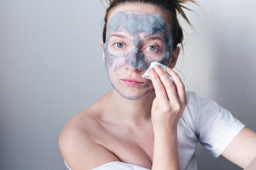 Beautiful young woman takes off a hydrating bubble mask