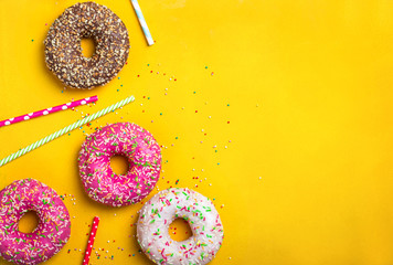 Wall Mural - Yellow dessert background with various donuts