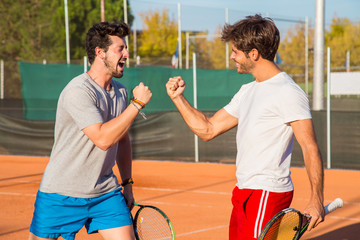 Two friends standing on tennis court and encouraging each other before match.