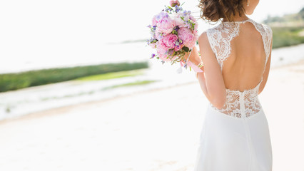 Beautiful bride on the seacoast. On the bride is a long wedding dress with lace and an open back. Bouquet in hands.