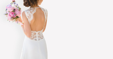 Beautiful bride on a gray background. On the bride is a long wedding dress with lace and an open back. Bouquet in hands.