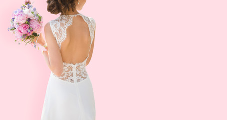 Beautiful bride on a pink background. On the bride is a long wedding dress with lace and an open back. Bouquet in hands.