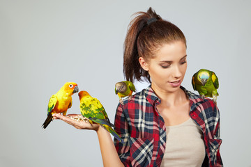 Woman feeding parrots. isolated shoot