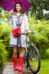 woman with an umbrella and a bicycle on a rainy day