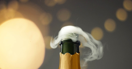 Close up slowmotion of man's hands opening a bottle of champagne on gray background with lights and flares