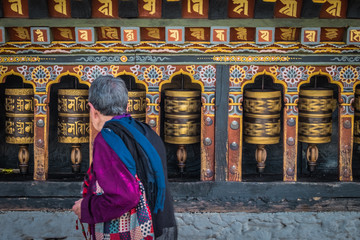 Old woman spinning prayer wheels in Thimphu, Bhutan