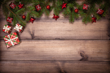 Christmas background with green fir branches, red gifts and stars on a wooden surface. Flat lay with copy space.