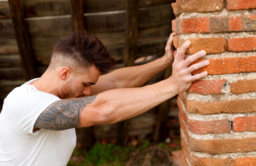 Attractive guy next to a brick wall