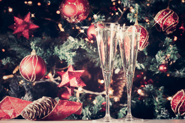 Wall Mural - Two glasses of champagne with Christmas tree background and sparkles. Holiday season background. Traditional red and green Christmas decoration