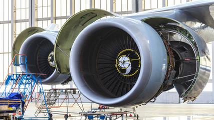 Aufnahme von Flugzeugtriebwerken von schräg vorne während der Wartung im Hangar mit aufgelappten Wartungsklappen