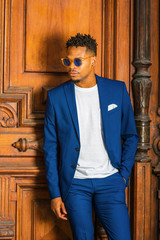 African American Businessman working in New York. Wearing blue suit, unbuttoned, white T shirt, blue sunglasses, college student with little goatee, standing by vintage doorway, looking down, thinking