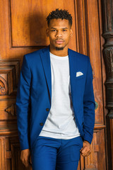 African American Businessman working in New York. Wearing blue suit, unbuttoned, white T shirt, black college student with little goatee, standing by vintage library doorway on campus, looking forward