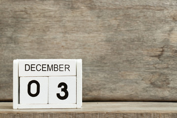 White block calendar present date 3 and month December on wood background