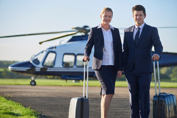 Portrait Of Businesswoman And Businessman Standing In Front Of Helicopter