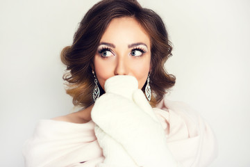 Beautiful girl in a Christmas image is surprised. Young woman in mittens and scarf with makeup and styling on white background.