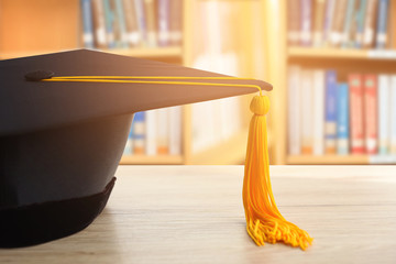 graduation cap with Yellow tassel on wood table ,The background is a blurred library.