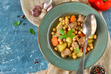 Homemade stew with potatoes, carrots and chickpeas on a blue background.