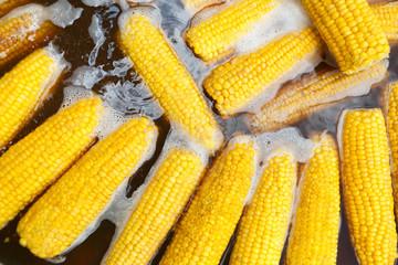 Fresh corncobs boiling in water closeup