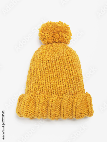3e6b5a6bffe Mustard knit beanie hat with big pom pom isolated on white background. Copy  space. Flat lay. Top view