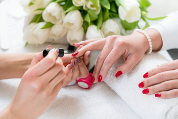 Hands of a skilled manicurist applying red nail polish on the nails of a young woman