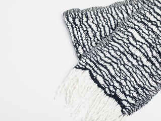 Black and white woolen striped scarf with fringe isolated on white background. Copy space. Flat lay. Top view
