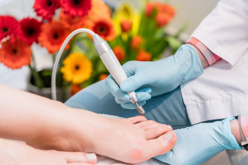 Close-up of the hands of a pedicurist wearing surgical gloves while using a toe nail clipper