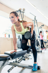 Low-angle view portrait of a beautiful fit woman smiling while exercising one-arm dumbbell row