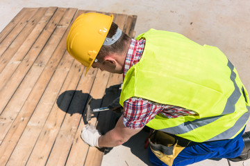 High-angle view of a blue-collar worker using a hammer on the construction site