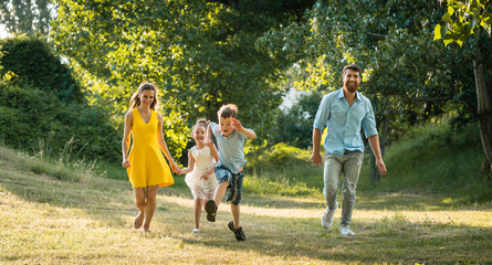 Active young parents with a healthy lifestyle running together with their two children
