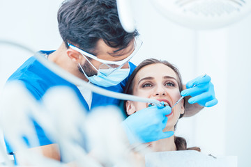 Young woman during painless oral treatment in the modern dental office of an experienced dentist