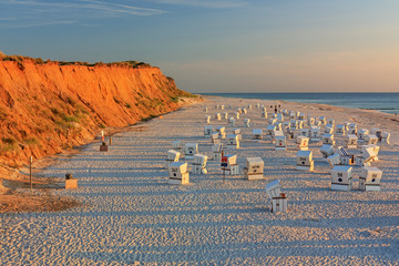 Strand mit Strandkörben am Roten Kliff bei Kampen auf Sylt an der Nordsee bei Sonnenuntergang