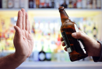 Hand rejecting alcoholic beer beverage bottle