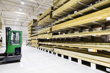 timber warehouse - shelves with wooden planks and forklift