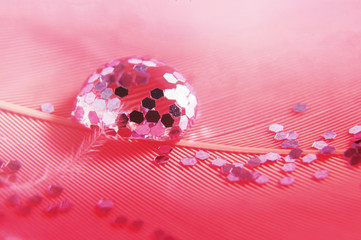 Drops with sparkles on a pink feather. Gentle soft beautiful artistic close-up photo. Bright abstract macro picture.