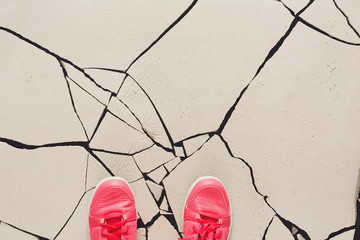 Pink shoes on cracked floor copy space