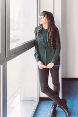 Young business woman looking standing near window looking outside - thinking, worried, inspiration concept