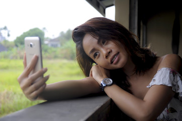 young beautiful Asian girl taking selfie picture with mobile phone camera smiling happy sitting outdoors at coffee shop