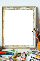 Mock up of vintage frame with brushes in art studio. Painting frame with empty place.
