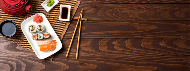 Set of sushi with red teapot and chopsticks
