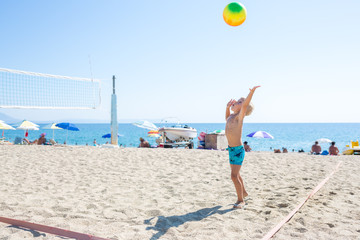 Little boy playing Beach Volleyball