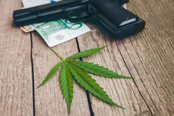 Cannabis leaf with gun and money bills