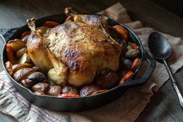whole baked chicken with potatoes and carrots in cast iron