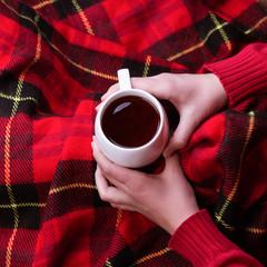 Hot mug of tea warming woman's hands in red woollen sweater.