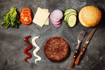 Homemade hamburger with ingredients on dark slate background top view