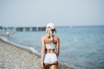 Back view of fitness girl walking along the beach