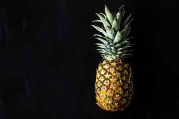 ripe whole pineapple on a black stone background. copy space